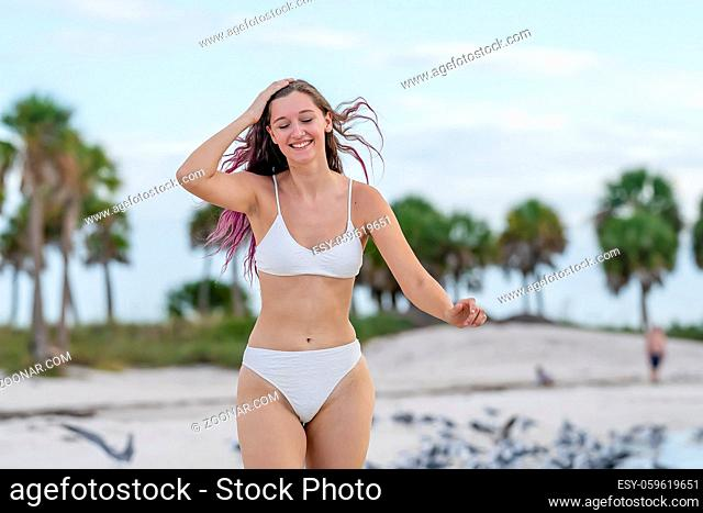 A beautiful brunette bikini model enjoys the weather outdoors on the beach while chasing seagulls