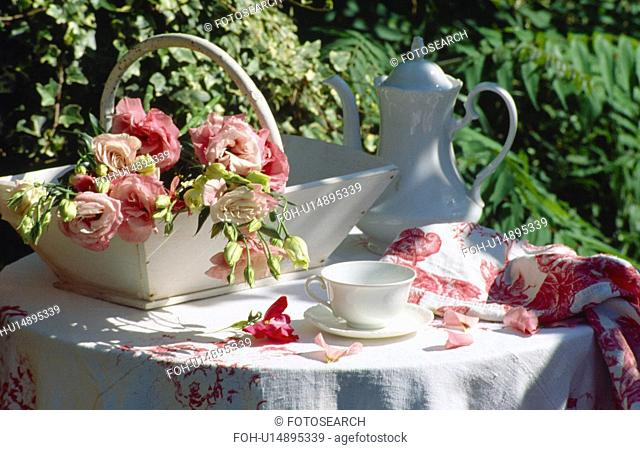 Still-life of pink roses in trug and white coffeepot on table with white linen cloth