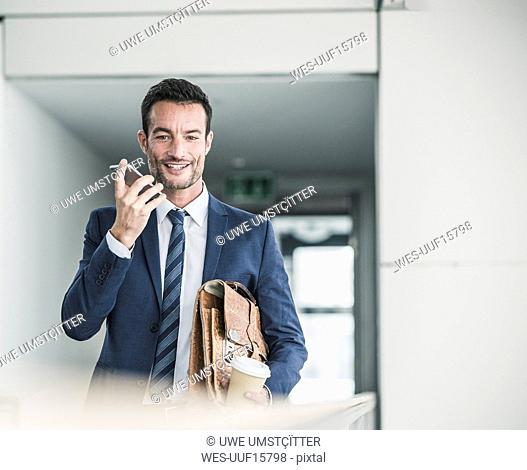 Businessman with briefcase walking in office building, using smartphone