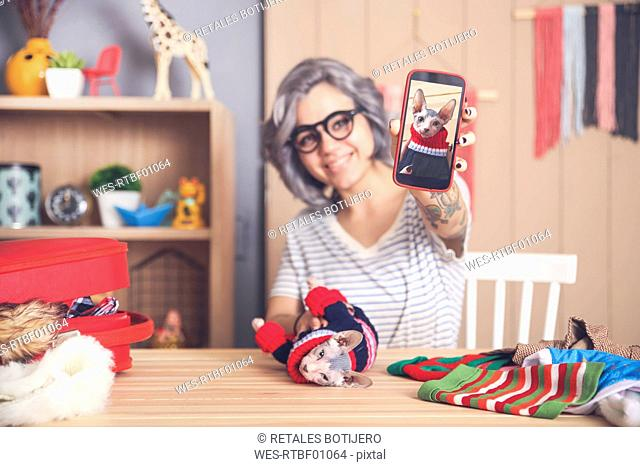 Woman showing cell phone picture of Sphynx cat wearing pullover