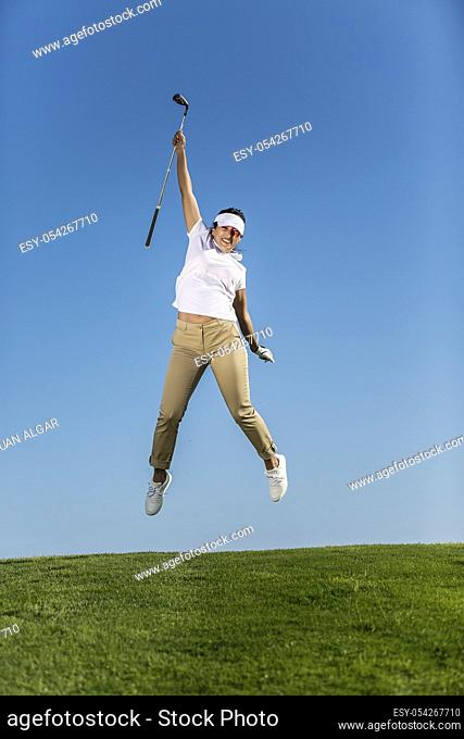 Beautiful excited woman holding golf driver and jumping high above green meadow of field against blue sky