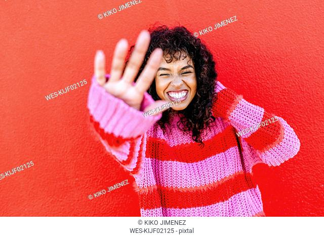 Portrait of laughing young woman in front of red wall