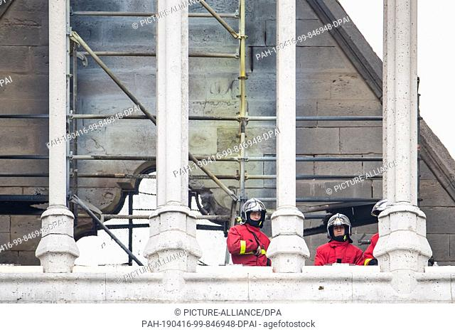 16 April 2019, France (France), Paris: Firemen are standing on the roof of Notre-Dame Cathedral. A fire broke out in the world-famous cathedral Notre-Dame in...