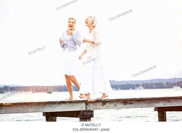 Two female friends walking along pier, laughing
