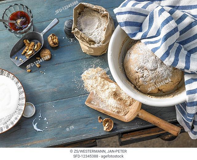 A loaf of bread, flour, barley malt, and walnuts