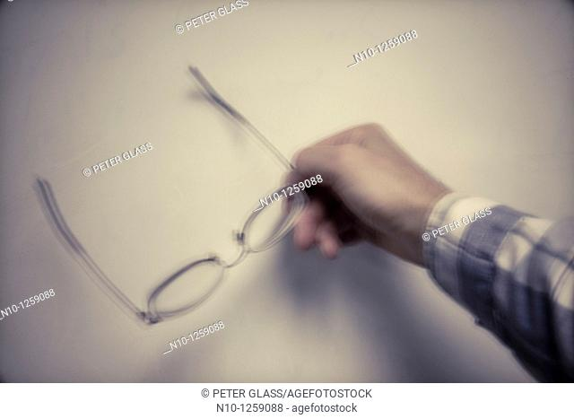 Man holding his glasses in front of a classroom whiteboard