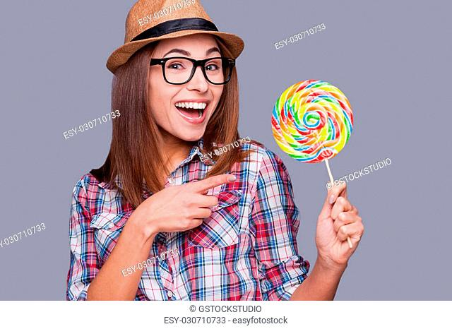 Sweet and extremely big. Beautiful young woman in funky hat holding a big lollipop and pointing on it while standing against grey background
