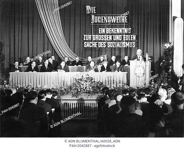 The letters in front of the curtain/behind the podium translate: 'The 'Jugendweihe' - A commitment to the grand and noble cause of socialism'