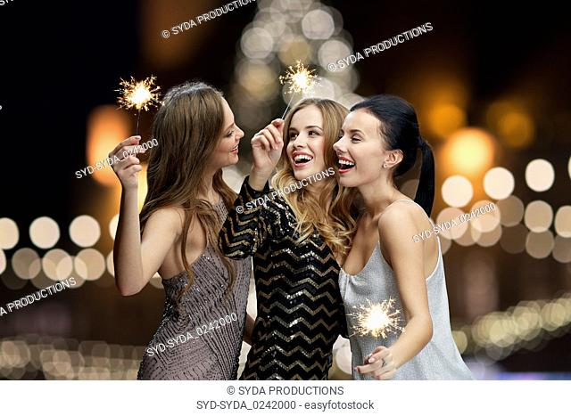 happy young women with sparklers at new year night