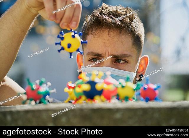 Caucasian man with a protective mask and catching virus models. The concept of Coronavirus