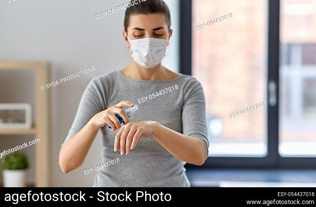 close up of woman in mask spraying hand sanitizer