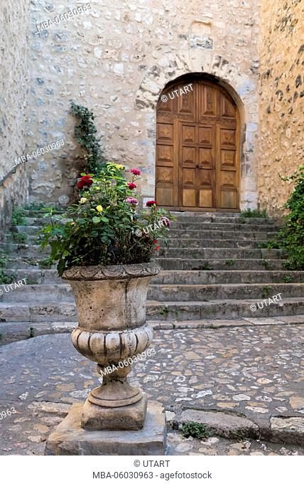 Village view, plant tub with blossoms in front of inner courtyard and old door
