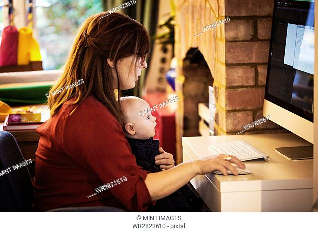 A woman seated with a baby on her lap using her computer, both watching the screen