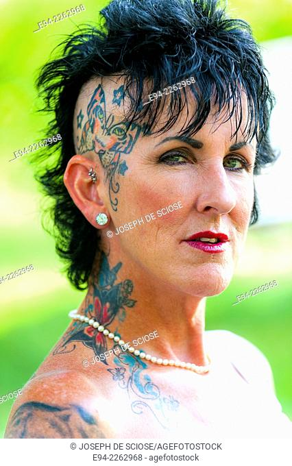 54 year old brunette woman with tattoos in outdoor setting looking directly at the camera