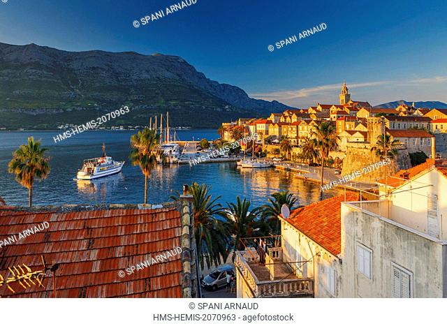 Croatia, Dalmatia, Dalmatian coast, Korcula Island, Korcula, view of a fortified village by the sea with yachts moored at sunset