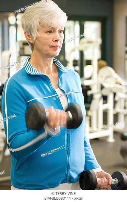 Mixed race woman exercising in health club