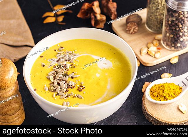 Close up of homemade pumpkin soup with sunflower and sesame seeds, coconut milk, nutmeg and yellow curry in a ceramic bowl