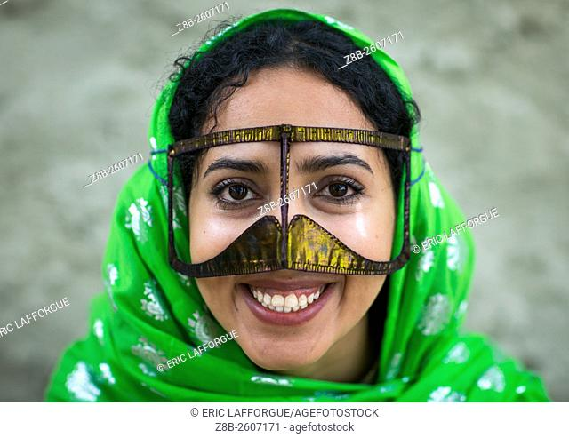 Iran, Qeshm Island, Salakh, a smiling bandari woman wearing a traditional mask called the burqa with a moustache shape