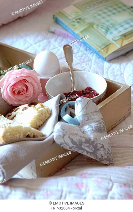 Tray with jam, egg, currant bun and rose on bed