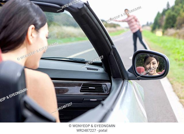 Young smiling woman in a car watching a male hitchhiker at roadside