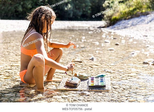Girl sitting in water of a river painting on stone