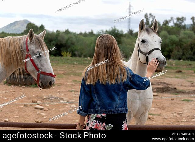 Girl with long dark blond hair strokes horse, gesture of trust
