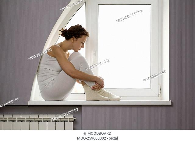 Mid adult woman sits on windowsill with ankles crossed