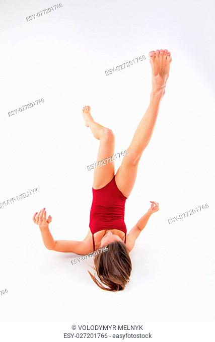 Young beautiful dancer in beige dress dancing on white studio background