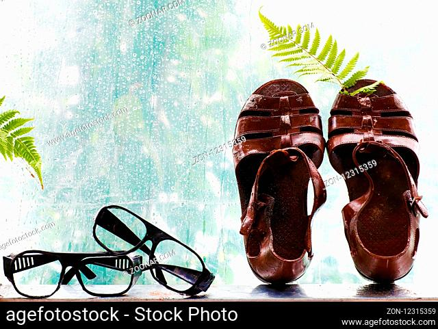 Couple of plastic sandals beside on window with rainy background, rain drops in rainy day, cyan color make beautiful and art scene