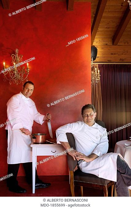 Italian chefs Enrico Cerea known as Chicco (sitting at the table) and Roberto Cerea (standing with a knife) in a photocall shooted at his restaurant awarded...