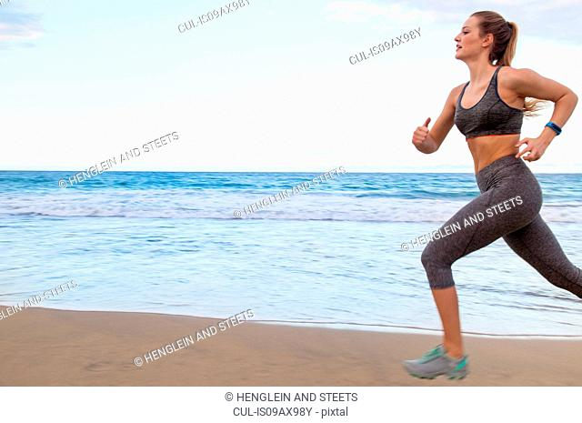 Young female runner running along beach, Dominican Republic, The Caribbean