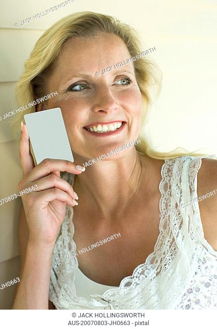 Close-up of a mature woman holding a credit card and smiling