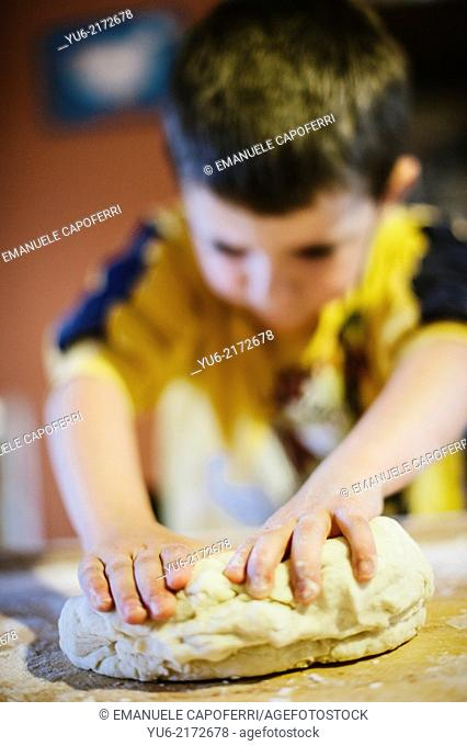 Child kneads the ingredients to make a cake