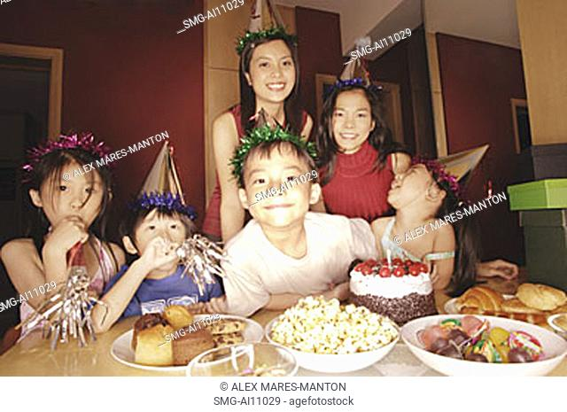 Young boy at a birthday party, surrounded by friends