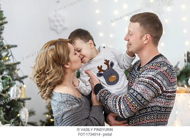 Father and mother with son at home during Christmas