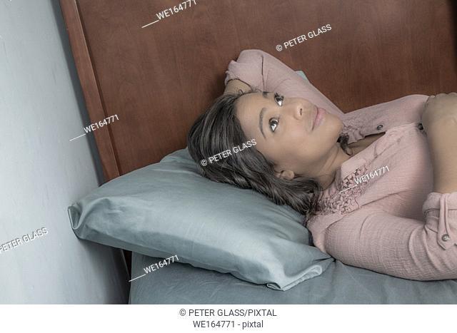 Young Hispanic woman lying on her bed