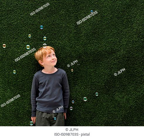 Boy in front of artificial grass smiling at bubbles