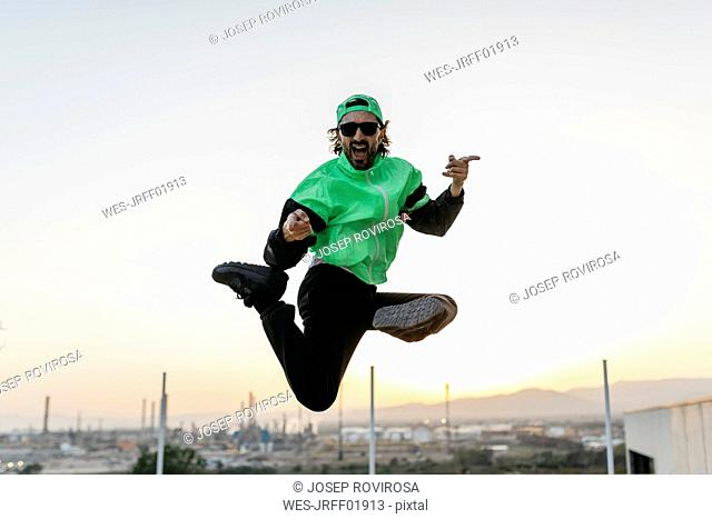 Man doing breakdance in urban concrete building, jumping mid air