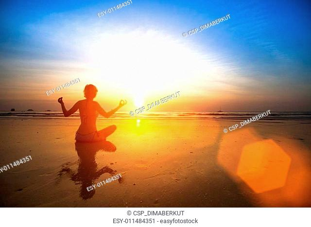 Silhouette yoga woman sitting on sea coast at beautiful sunset