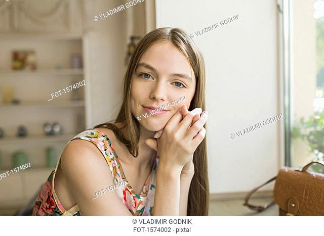 Portrait of smiling beautiful woman leaning on table by window