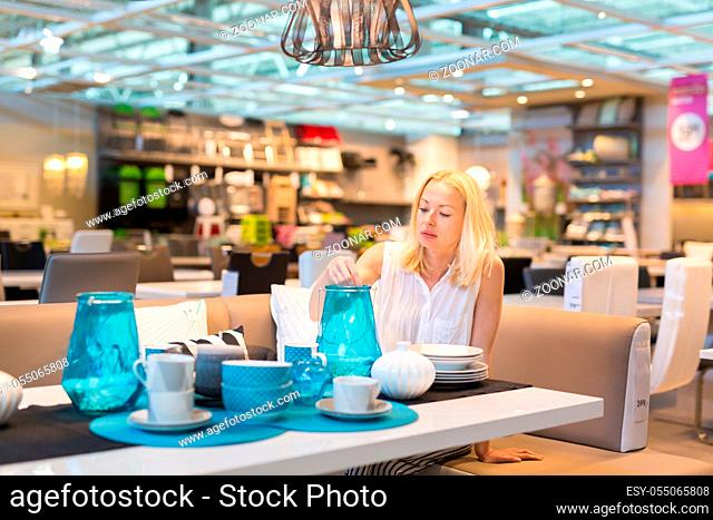 Beautiful young caucasian woman choosing the right item for her apartment in a modern home decor furnishings store. Shopping in retail store