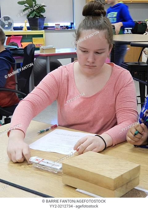 8th Grade Girl Doing Science Friction Experiment, Wellsville, New York, USA