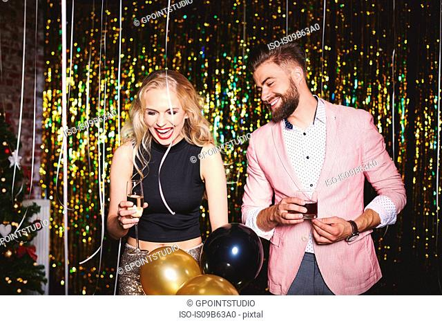 Man and woman at party, holding drinks, laughing