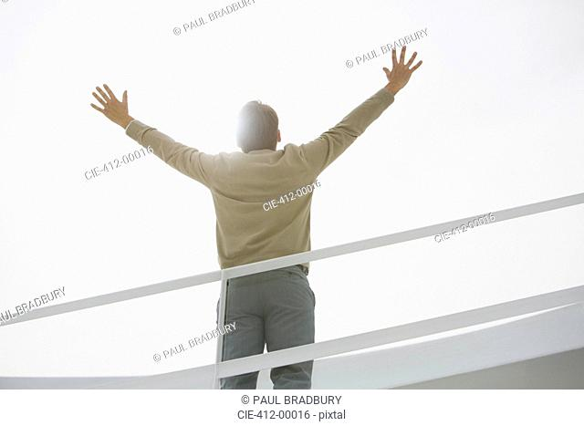 Sun shining behind businessman with arms raised