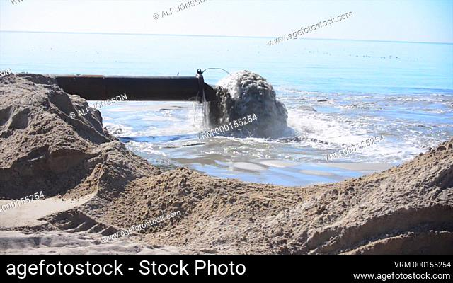 Excavator working with beach repair and restoring by sand from bottom ot the Baltic Sea in Ystad, Scania, Sweden