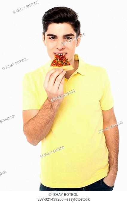 Happy young casual boy eating pizza