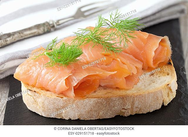 Smoked salmon with fresh dill on bread slice, in natural light, authentic food