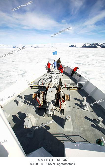 The National Geographic Endeavour breaking through fast ice in the Weddell Sea around the Antarctic Peninsula Guests are on the bow watching the process