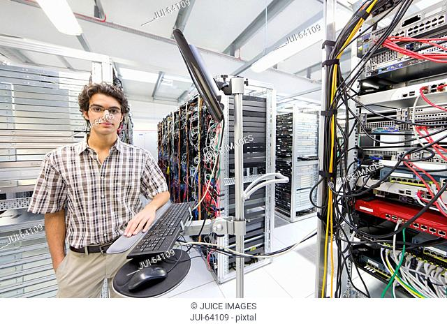 Technician, looking at camera, standing near computer in Server room of data center