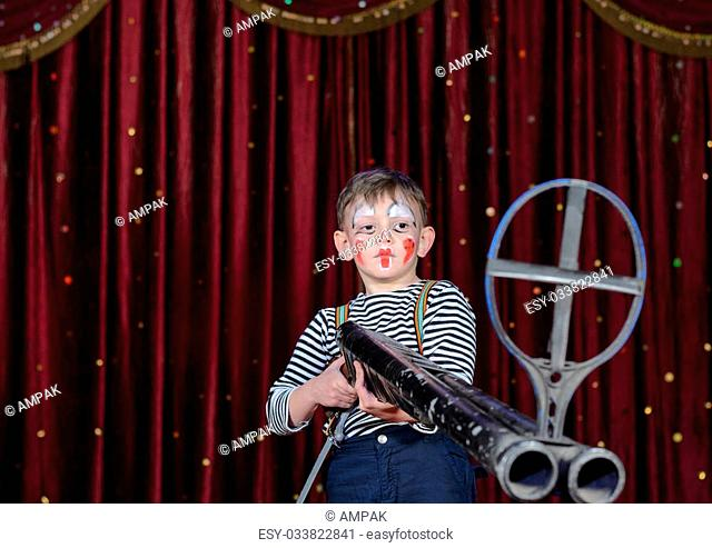 Young Boy Wearing Clown Make Up Standing on Stage Aiming Large Prop Shot Gun Rifle in front of Red Curtain